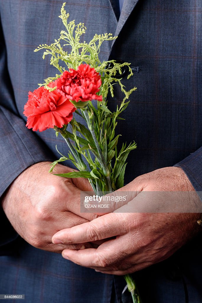 A picture taken at the explosion site at Istanbul's Ataturk airport International terminal on July 1, 2016 shows hands holding cloves as Consuls of European countries laid flowers three days after a suicide bombing and gun attack targeted the airport, killing 44 people. Although no group has yet claimed Tuesday's gun and bomb attack which killed 42 people, Ankara has pointed a finger at IS, which has been blamed for several suicide attacks around the country in the past year. / AFP / OZAN