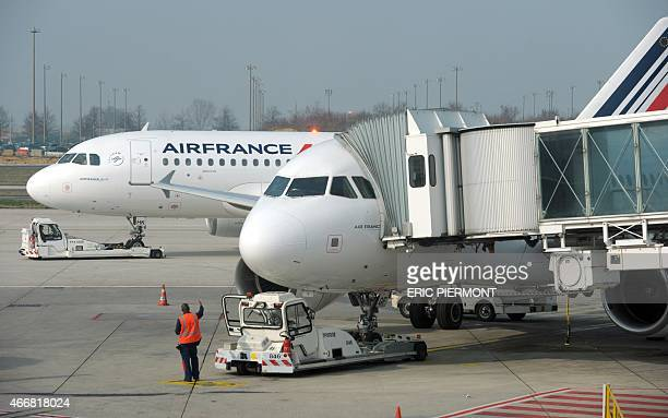 A picture taken behind a window shows Air France planes on the tarmac at Roissy Charles de Gaulle airport on March 18 2015 AFP PHOTO ERIC PIERMONT
