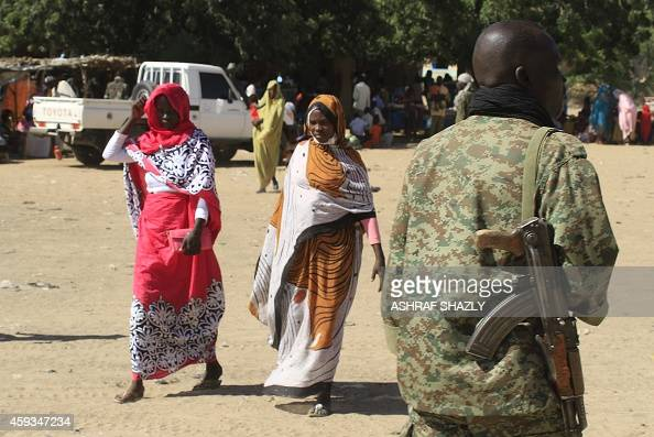 A picture taken during a government organised tour shows Sudanese troop stading guard near villagers in Tabit in the North Darfur on November 20 2014...