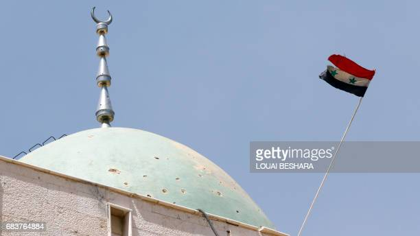 A picture taken during a tour provided by Syrian government forces on May 16 2017 shows a national flag flying over the Ghofran mosque in Damascus'...