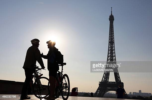 Picture taken early in the morning on September 27 2015 shows two men with bikes chating in front of the Eiffel Tower before taking part in the...