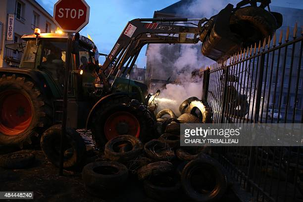 A picture taken early on August 19 2015 shows a tractor stacking tires in front of the prefecture as farmers protest in SaintLo northwestern France...