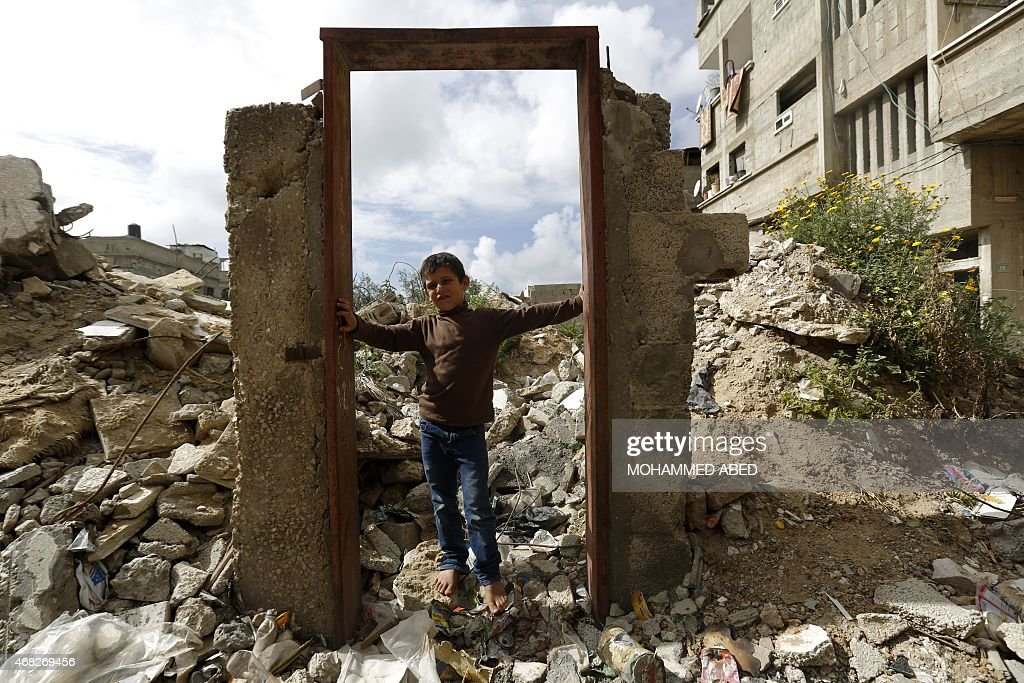 A picture taken east of Jabalia in the northern Gaza Strip on April 1 shows a Palestinian boy standing in a doorway that previously housed a mural of...