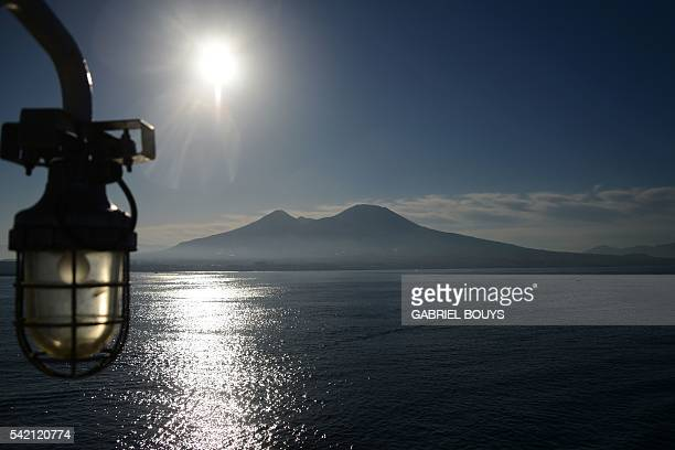 A picture taken from a ferry shows the volcano Vesuvius at sunrise on June 21 in the Gulf of Naples AFP PHOTO / GABRIEL BOUYS / AFP / GABRIEL BOUYS