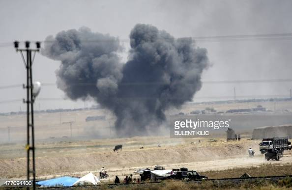 A picture taken from Akcakale in Turkey shows black smoke billowing into sky after an airstrike during clashes in the eastern part of the Syrian town...