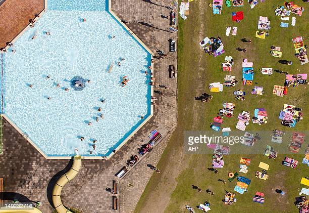 A picture taken from an Octocopter a remote controlled helicopter shows an aerial view of sunbathers and swimmers at De Tongelreeps swimming pool in...