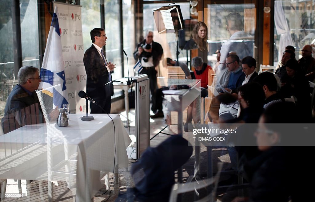 A picture taken from behind a window shows Israeli co-leader of the Zionist Union party and Labour Party's leader Isaac Herzog (C) speaking during a press conference at the Jerusalem Press Club, on February 10, 2016. / AFP / THOMAS COEX