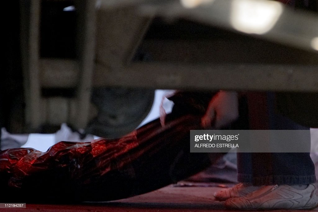 Picture taken from below a vehicle of forensic personnel downloading on April 14, 2011 in Mexico City a bag with the body of one of the seventy-six people murdered in Matamoros, Tamaulipas state, Mexico. Investigators found 10 more bodies Wednesday in a series of mass graves in northeastern Mexico, bringing the total to 126 in a case officials have blamed on the Zetas drug cartel. AFP PHOTO/Alfredo Estrella