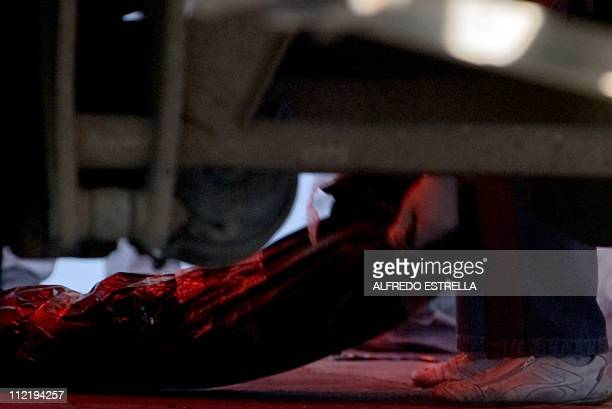 Picture taken from below a vehicle of forensic personnel downloading on April 14 2011 in Mexico City a bag with the body of one of the seventysix...