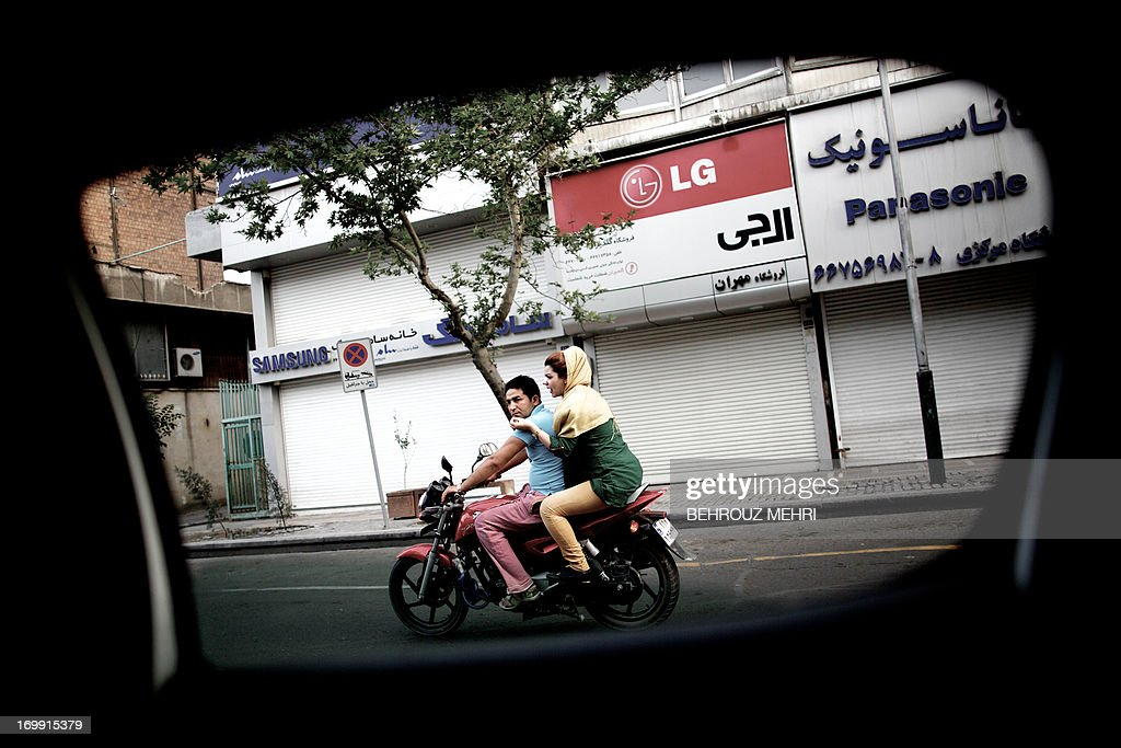 A picture taken from inside a car shows an Iranian couple riding a motorcycle on Jomhouri street in downtown Tehran on June 4 2013 AFP PHOTO/BEHROUZ...