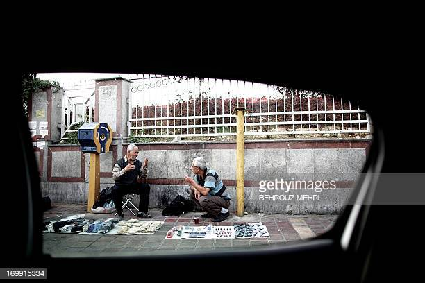 A picture taken from inside a car shows Iranians vendors drinking tea on a sidewalk in Azadi square in western Tehran on June 4 2013 AFP...