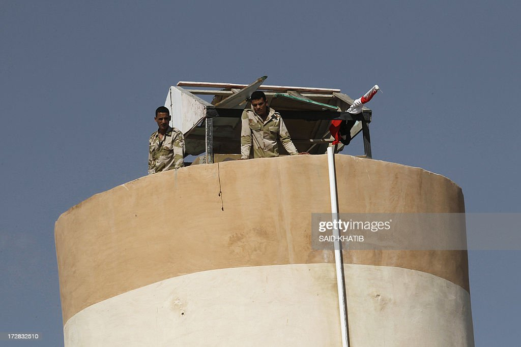 A picture taken from Rafah in the southern Gaza Strip on the border with Egypt, on July 5, 2013 shows two Egyptian soldiers standing on top of a watch tower. An Egyptian soldier was killed early today in coordinated rocket and machinegun attacks by Islamist militants on army checkpoints and a police base in the restive Sinai, medics said.