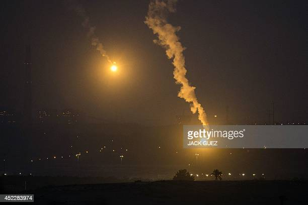 A picture taken from the Israeli Gaza border shows an Israeli army flare illuminating the sky above the Gaza strip on July 17 2014 Israeli air...