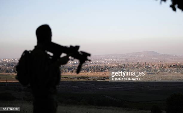 A picture taken from the Israeliannexed Golan Heights on August 21 2015 shows an Israeli soldier standing guard along the ceasefire line separating...