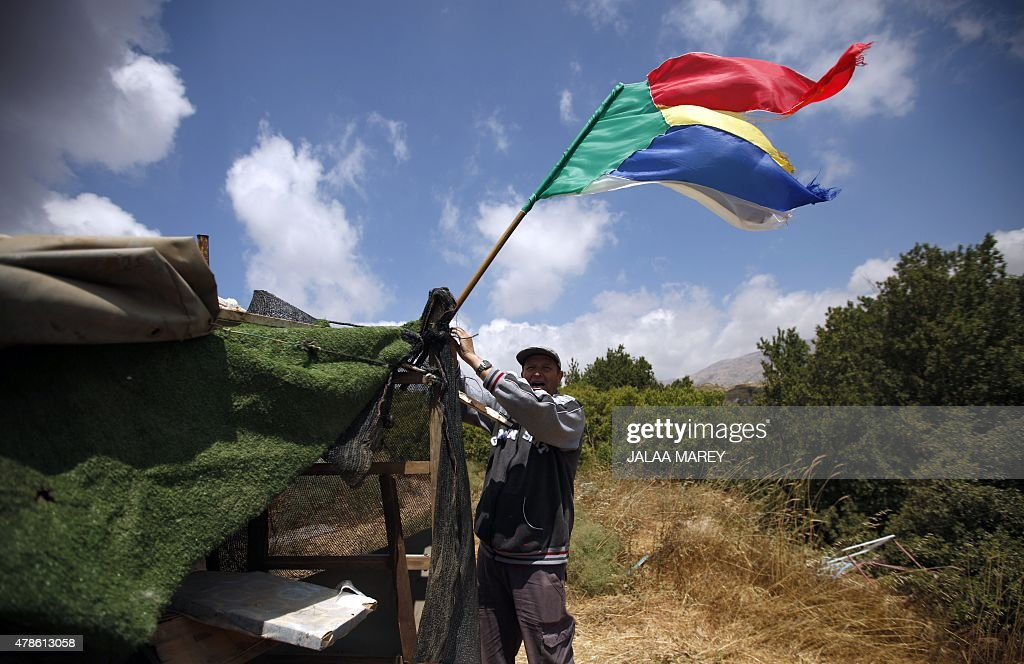 A picture taken from the Israeliannexed Golan Heights shows a Druze man residing in Israel holding his community's flag as others gather to watch...