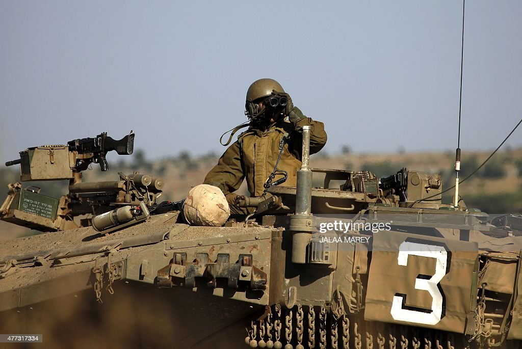 A picture taken from the Israeliannexed Golan Heights shows an Israeli soldier monitoring the Syrian Druze village of Hader in the Syrian side of the...