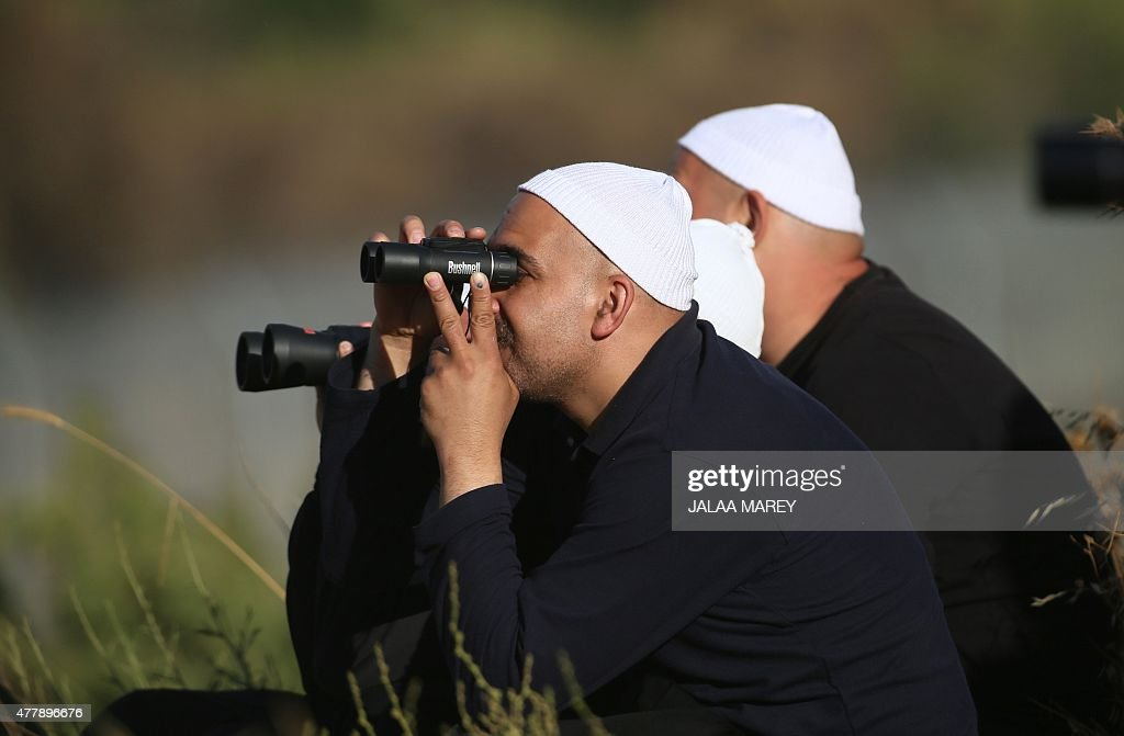 A picture taken from the Israeliannexed Golan Heights shows Druze men residing in Israel holding binoculars watching smoke rising in the horizon of...