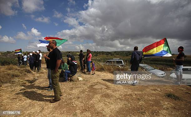 A picture taken from the Israeliannexed Golan Heights shows Druze men residing in Israel holding their community's flag and gathering to watch smoke...