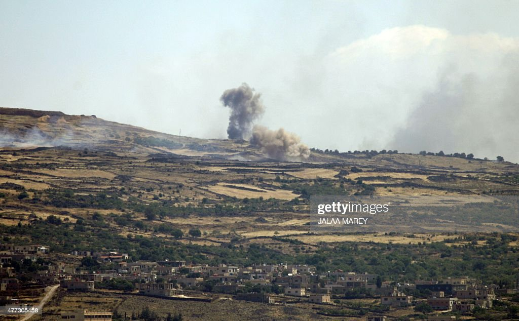 A picture taken from the Israeliannexed Golan Heights shows smoke rising from the Syrian Druze village of Hader on June 16 2015 AlNusra Front one of...