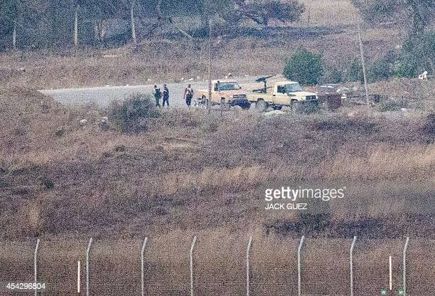 A picture taken from the Israelioccupied Golan Heights shows armed men reportedly rebel fighters standing near vehicles in the Syrian side of the...