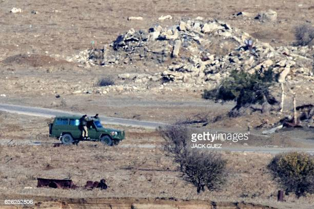 A picture taken from the Israelioccupied Golan Heights shows armed men reportedly rebel fighters standing on the sides of a vehicle in the Syrian...