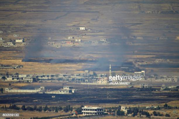 TOPSHOT A picture taken from the Israelioccupied Golan Heights shows smoke billowing from the Syrian side of the border on June 24 2017 An Israeli...