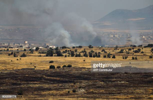 A picture taken from the Israelioccupied Golan Heights shows smoke billowing from the Syrian side of the border on June 24 2017 An Israeli aircraft...