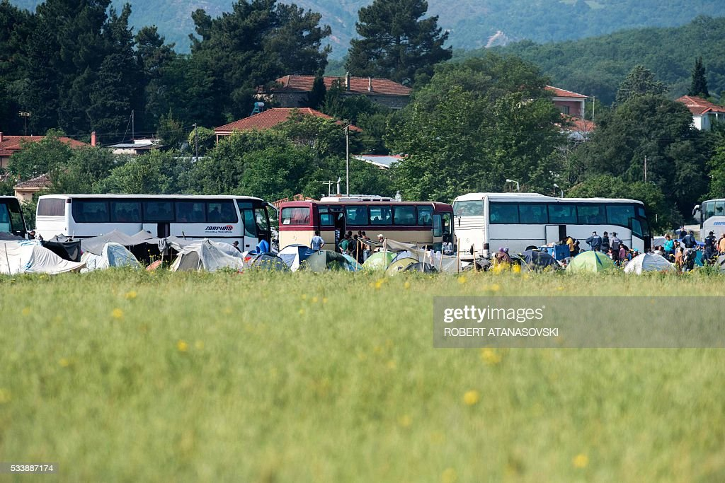A picture taken from the Macedonian side near Gevgelija on May 24, 2016 at the Greek-Macedonian border, shows the evacuation operation by Greek police officers of a makeshift migrant camp near the village of Idomeni. In an operation which began shortly after sunrise on May 24, hundreds of Greek police began evacuating the sprawling camp which is currently home to 8,400 refugees and migrants, among them many families with children, an AFP correspondent said. At its height, there were more than 12,000 people crammed into the site, many of them fleeing war, persecution and poverty in the Middle East and Asia, with the camp exploding in size since Balkan states began closing their borders in mid February in a bid to stem the human tide seeking passage to northern Europe. / AFP / Robert ATANASOVSKI