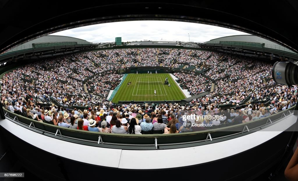 A picture taken from the roof of No. 1 court shows Canada's Milos Raonic play against Germany's Jan-Lennard Struff during their men's singles first round match on the second day of the 2017 Wimbledon Championships at The All England Lawn Tennis Club in Wimbledon, southwest London, on July 4, 2017. / AFP PHOTO / Justin TALLIS / RESTRICTED