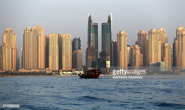 A picture taken from the sea on May 23 2015 shows a traditional dhow sailing in front of the Jumeirah Beach Residence in Dubai AFP PHOTO/MARWAN...