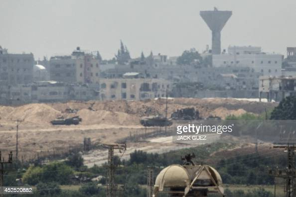 A picture taken from the southern Israeli Gaza border shows Israeli army Merkava tanks and armoured personnel carriers holding a postion inside the...