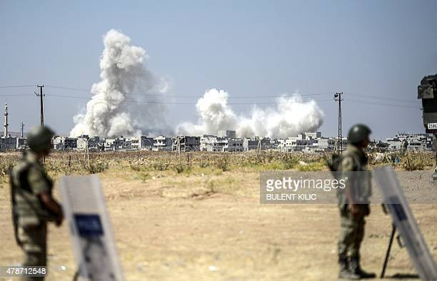 A picture taken from the Turkish side of the border in Suruc Sanliurfa province shows Turkish soldiers standing as smoke rises from the Syrian town...
