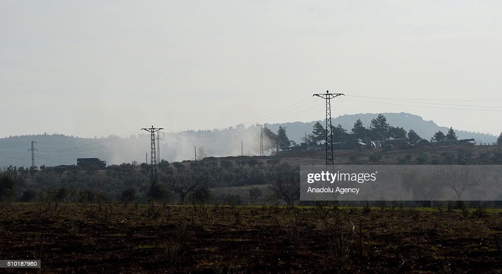 A picture taken from Turkish side of Syrian border shows that smoke rises as Turkish Army howitzers shell YPG terrorists' targets which placed in the Azaz Town of Syria's Aleppo, from an emplacement near Syrian border in Turkey's Kilis province on February 14, 2016. YPG is the armed wing of PYD. The PYD terrorist organization is affiliated to the PKK, a terrorist organization which has fought Turkey since 1984 in a conflict that has caused more than 40,000 deaths. The PKK is listed as a terrorist organization by Turkey, the U.S. and EU.
