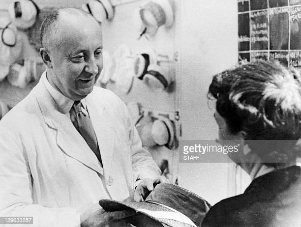 Picture taken in 1956 of French designer Christian Dior presenting a hat to a person unidenfied in his atelier in Paris