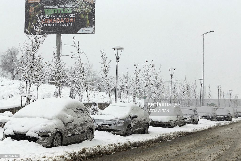 A picture taken in Ankara on February 6, 2016 shows snow-covered cars parked by the road. / AFP / ADEM ALTAN