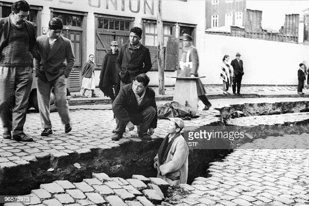 picture taken in April 1960 in Valdivia of people looking at an enormous crack on a street due to the earthquake that struck the area on May 22 1960...