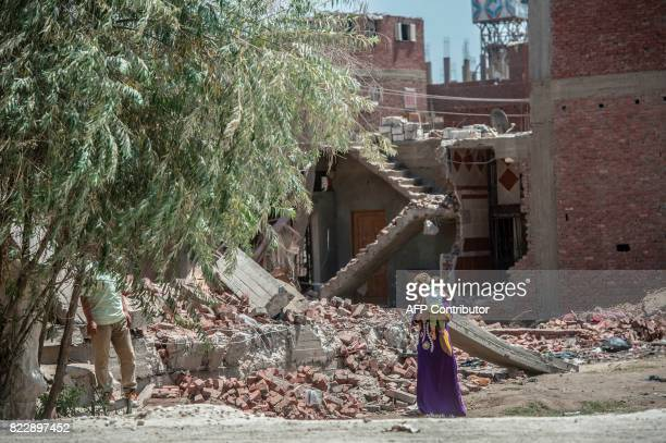 A picture taken in Cairo on July 20 2017 shows a woman carrying a baby next to the rubble of a house that was demolished Cairo's Warraq island As...