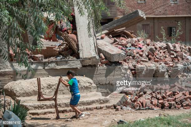 A picture taken in Cairo on July 20 2017 shows an Egyptian child playing with a chair next to the rubble of a house that was demolished Cairo's...