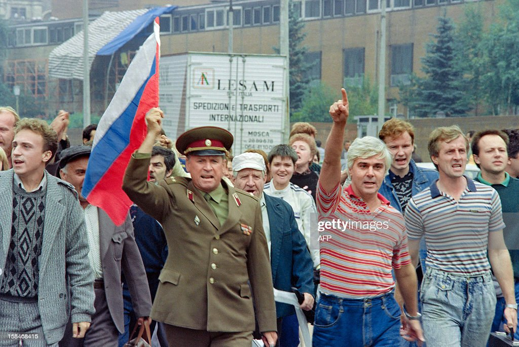 A picture taken in Moscow on August 20 1991 shows a group of Yeltsin supporters including a Soviet colonel with the Russian flag walking towards the...