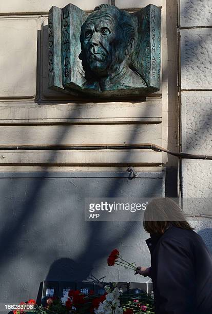 A picture taken in Moscow on October 30 shows a women laying flowers at a commemorative plaque in memory of author and former Gulag prisoner Varlam...