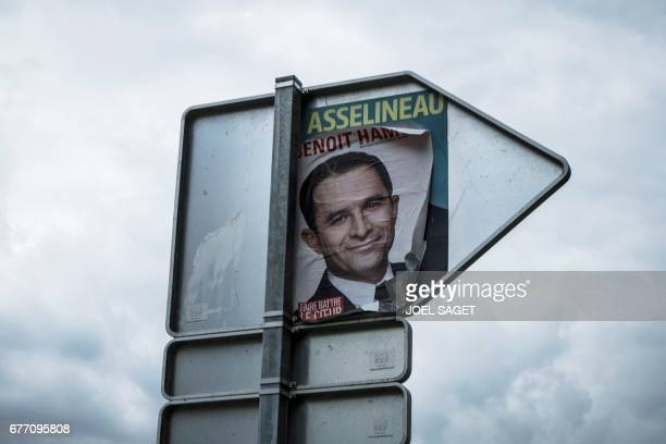 A picture taken in Paris on May 2 2017 shows a campaign poster of French presidential election candidate for the leftwing French Socialist party...
