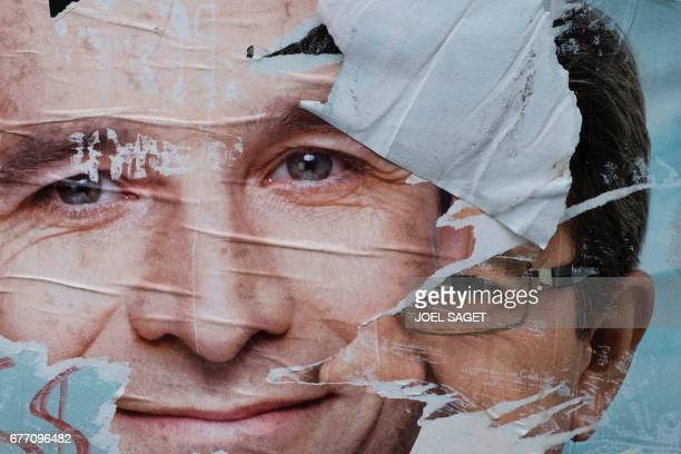 A picture taken in Paris on May 2 2017 shows vandalised campaign posters of French presidential election candidate for the leftwing French Socialist...