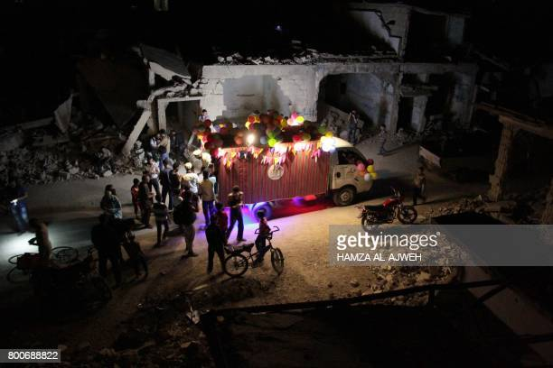 TOPSHOT A picture taken in the early hours of June 25 2017 shows Syrians gathered around an icecream vehicle amid destroyed buildings on the last day...