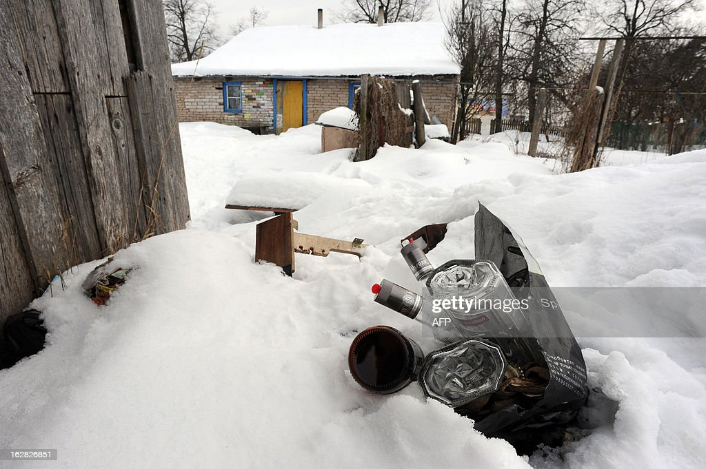 A picture taken in the Russian town of Gdov, 700 km northwest of Moscow, on February 26, 2013, shows a bag with empty vodka bottles lying in front of the house of Yulia Kuzmina, the biological mother of Maxim Kuzmin, also known as Max Shatto, a Russian boy who was adopted by a Texan couple last fall and died in January.