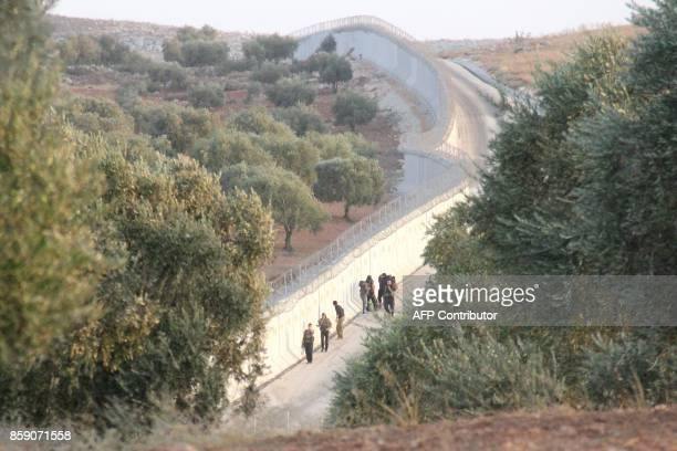 TOPSHOT A picture taken in the Syrian village of Aqrabat in the Harem district of Idlib province on the border with Turkey on October 8 shows...