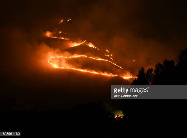 A picture taken late on August 9 2017 shows as car driving on a road as flames and smoke rise from a forest in fire near Sarande in the Muzina...