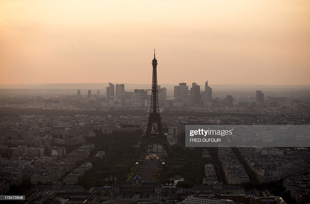A picture taken late on July 14, 2013 shows the Eiffel tower in Paris and the business district of La Defense in the background. AFP PHOTO / FRED DUFOUR
