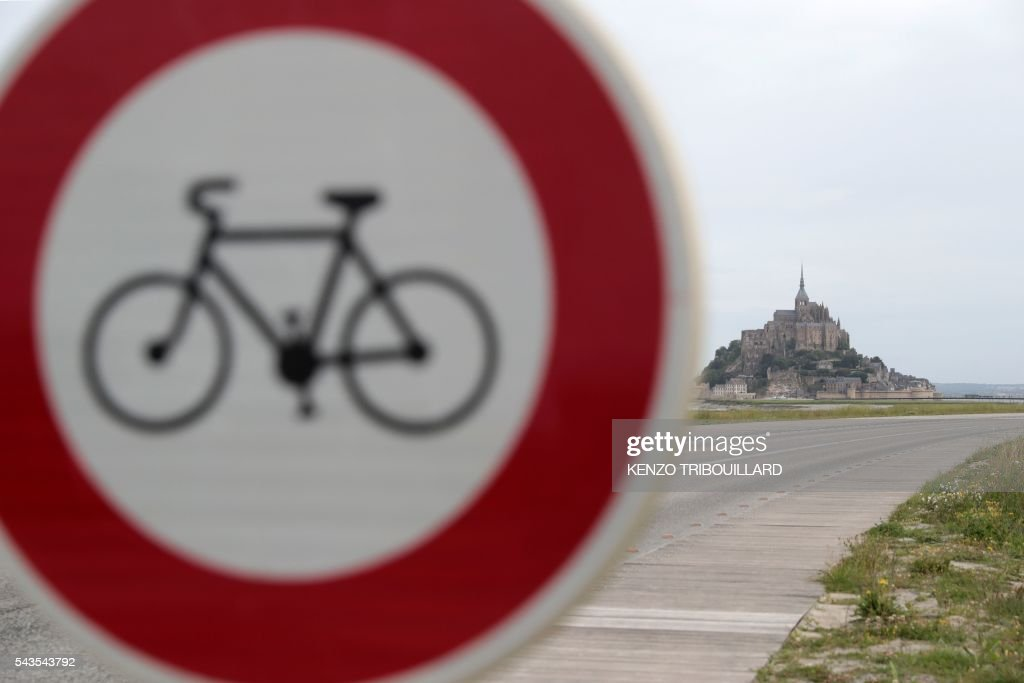 Picture taken of a road sign indicating that cycling is prohibited beyond, near Le Mont-Saint-Michel (background), on June 29, 2016, three days before the start of the 103rd edition of the Tour de France cycling race. The 2016 Tour de France will start on July 2 in the streets of Le Mont-Saint-Michel and ends on July 24, 2016 down the Champs-Elysees in Paris. / AFP / KENZO