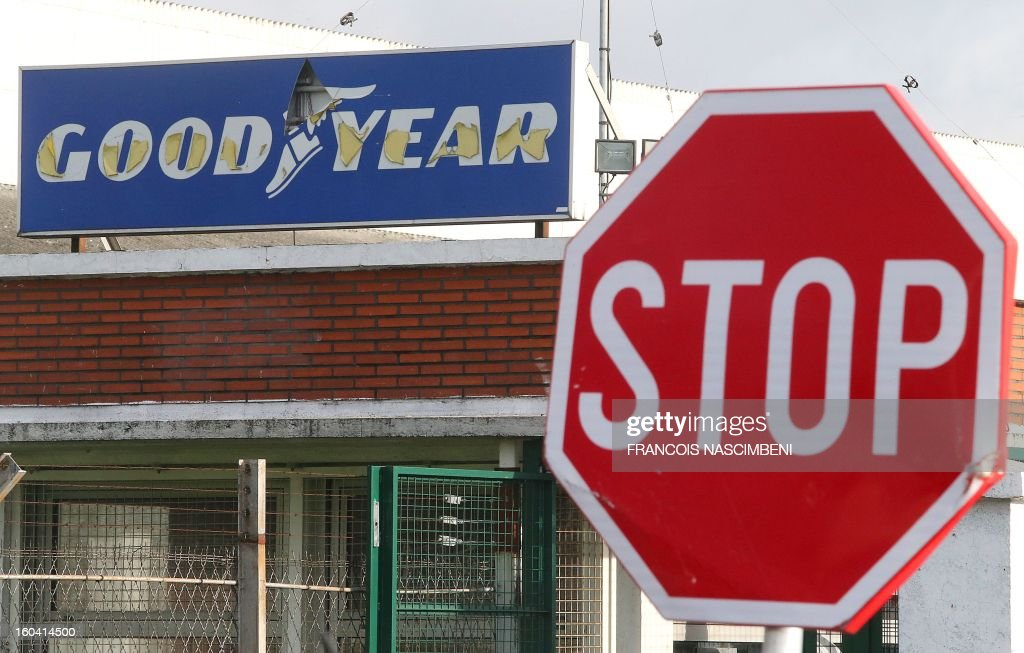 Picture taken of a stop road sign in front of the entrance of the US tyre manufacturer Goodyear plant in Amiens, northern France, on January 31, 2013. Executives at a Goodyear tyre plant in Amiens presented today a plan to close the site, which employs 1,173 workers. 'Closing the factory is the only option after five years of unsuccessful negotiations,' said a statement, which added that the plan had been presented to a works committee and would serve as the basis for further consultations with workers' representatives. AFP PHOTO / FRANCOIS NASCIMBENI