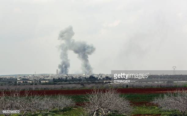 A picture taken on April 1 2017 shows smoke plumes rising near the town of Qumhanah in the countryside of the central province of Hama as Syrian...